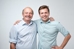 Hispanic father and adult son hugging and smiling at camera. Good famile relations Stock Photos
