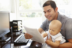 Hispanic father with baby working in home office Royalty Free Stock Photo