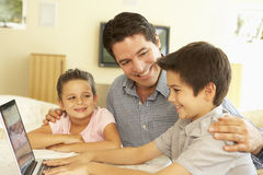 Hispanic Father And Children Using Computer At Home Stock Photography