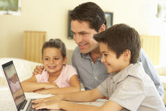 Hispanic Father And Children Using Computer At Home Stock Image