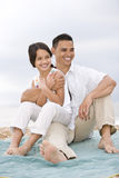 Hispanic father with little girl on beach blanket Stock Image
