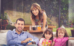 Hispanic father sitting in sofa with two daughters Royalty Free Stock Image
