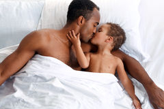 Hispanic Father with son in bed. Daddy kisses his son at bedtime, family relationship Royalty Free Stock Images