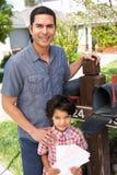 Hispanic Father And Son Checking Mailbox Stock Photo