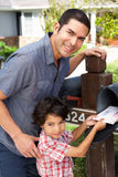Hispanic Father And Son Checking Mailbox Stock Photo