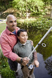 Hispanic father and son fishing in pond Stock Image