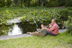 Hispanic father and son fishing in pond Stock Photography