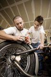 Hispanic father and son in garage Royalty Free Stock Images