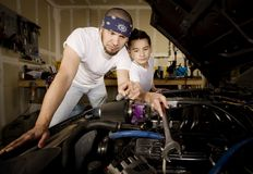 Hispanic father and son in garage Stock Photography