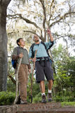 Hispanic father and son hiking in park Stock Photos