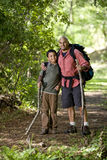Hispanic father and son hiking on trail in woods. Father and 10 year old son hiking on trail in woods royalty free stock image