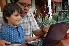 Hispanic father and son on laptop stock images