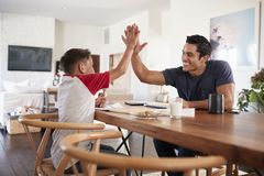 Hispanic father and son sitting opposite each other, high five over the dining room table, side view stock images
