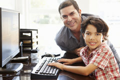 Hispanic father and son using computer at home stock images