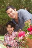 Hispanic Father And Son Working In Garden Tidying Pots Royalty Free Stock Photography
