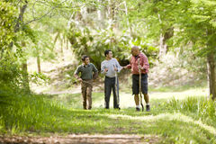 Hispanic father and sons hiking on trail in woods. Father and two sons hiking on trail in woods and talking stock photography
