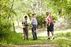 Hispanic father and sons hiking on trail in woods. Rear view of father and two sons hiking on trail in woods stock photography