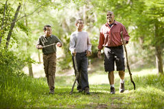 Hispanic father and sons hiking on trail in woods. Father and two sons hiking on trail in woods and talking royalty free stock images