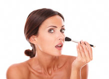 Hispanic female applying blush on her face Stock Images