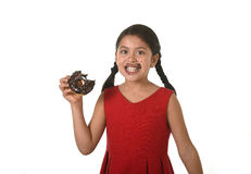 Hispanic female child in red dress eating chocolate donut with hands and mouth stained and dirty smiling happy Stock Images