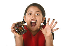 Hispanic female child in red dress eating chocolate donut with hands and mouth stained and dirty smiling happy. In kid loving sugar and sweet food concept stock photo