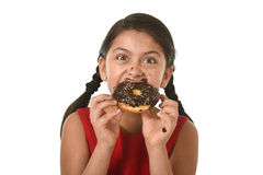 Hispanic female child in red dress eating chocolate donut with hands and mouth stained and dirty smiling happy. In kid loving sugar and sweet food concept stock images
