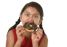 Hispanic female child in red dress eating chocolate donut with hands and mouth stained and dirty smiling happy Royalty Free Stock Photos