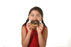 Hispanic female child in red dress eating chocolate donut with hands and mouth stained and dirty smiling happy Stock Image