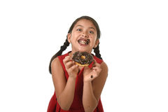 Hispanic female child in red dress eating chocolate donut with hands and mouth stained and dirty smiling happy Stock Photography