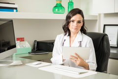 Hispanic female doctor using a tablet Stock Images