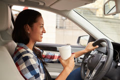 Hispanic female driver holding take away drink, in car view Stock Photos