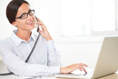 Hispanic female employee conversing on the phone Royalty Free Stock Photography