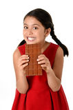 Hispanic female girl wearing red dress holding with both hands big chocolate eating in happy excited face expression in sugary nut Stock Photos