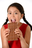 Hispanic female girl wearing red dress holding with both hands big chocolate eating in happy excited face expression in sugary nut Royalty Free Stock Photos