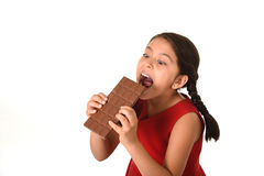 Hispanic female girl wearing red dress holding with both hands big chocolate eating in happy excited face expression in sugary nut. 7 or 8 years old Hispanic Royalty Free Stock Photography