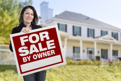 Hispanic Female Holding Sale By Owner Sign In Front of House. Smiling Hispanic Female Holding For Sale By Owner Sign In Front of Beautiful House Royalty Free Stock Images