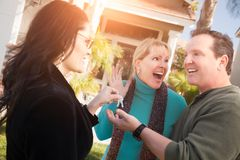 Hispanic Female Real Estate Agent Handing Over New House Keys to Happy Couple In Front of House royalty free stock photography
