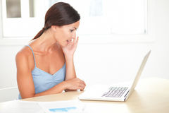 Hispanic female surprised while working on laptop Royalty Free Stock Photography