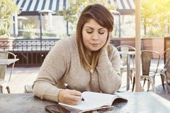 Hispanic Female Writting in Her Journal in an Outdoor Cafe royalty free stock images