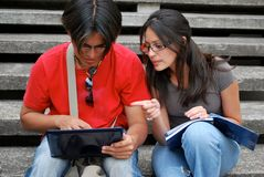 Hispanic friends looking at laptop together. Hispanic students studying together on the steps of a college campus Stock Image