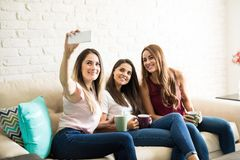 Hispanic friends taking a selfie. Three pretty Hispanic friends having some coffee at home and taking a selfie Stock Photo