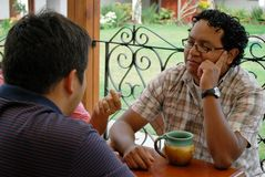 Hispanic friends talking. Young Hispanic friends talking together at a cafe Stock Photo