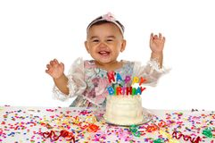 Hispanic girl and birthday cake 1 year old. An adorable one-year-old hispanic baby girl laughing over a birthday cake with letter candles Royalty Free Stock Photography