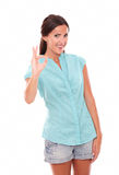 Hispanic girl in blue blouse gesturing a great job Royalty Free Stock Image