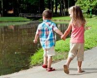 Hispanic girl and boy walk around pon Stock Photography
