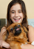 Hispanic girl carrying her small pekingese dog Stock Photo