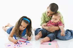 Hispanic girl coloring with brothers. Young latino girl coloring on construction paper while brothers watch Royalty Free Stock Photos
