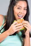Hispanic girl eating burger with lettuce. Cheerful young Latina woman eating burger during lunch break Royalty Free Stock Image