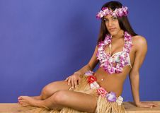 Hispanic girl in a flower lay and grass skirt. Blue background Royalty Free Stock Photography