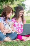 Hispanic girl and her mother browsing the web outdoors Royalty Free Stock Photography